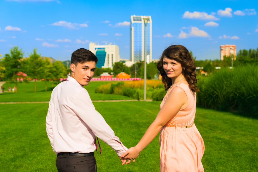 The young happy couple walking in the city park on grass and holding hands in summer.